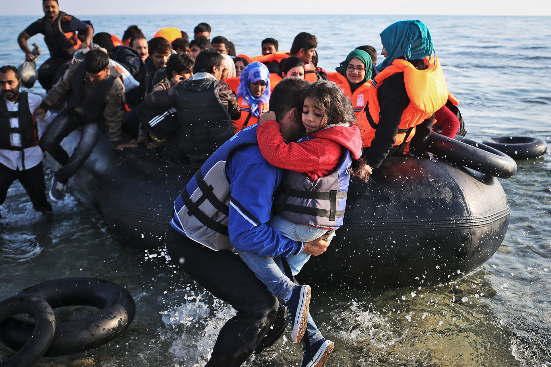 Syrian refugees come in on a boat from Turkey, in Mytilene, on the island of Lesbos, Greece on Friday, October 9th, 2015. Once refugees get processed and get papers after their arrival in Lesbos, they can exchange money and buy ferry tickets to get to Athens.(Photo credit/Tara Todras-Whitehill for IRC)