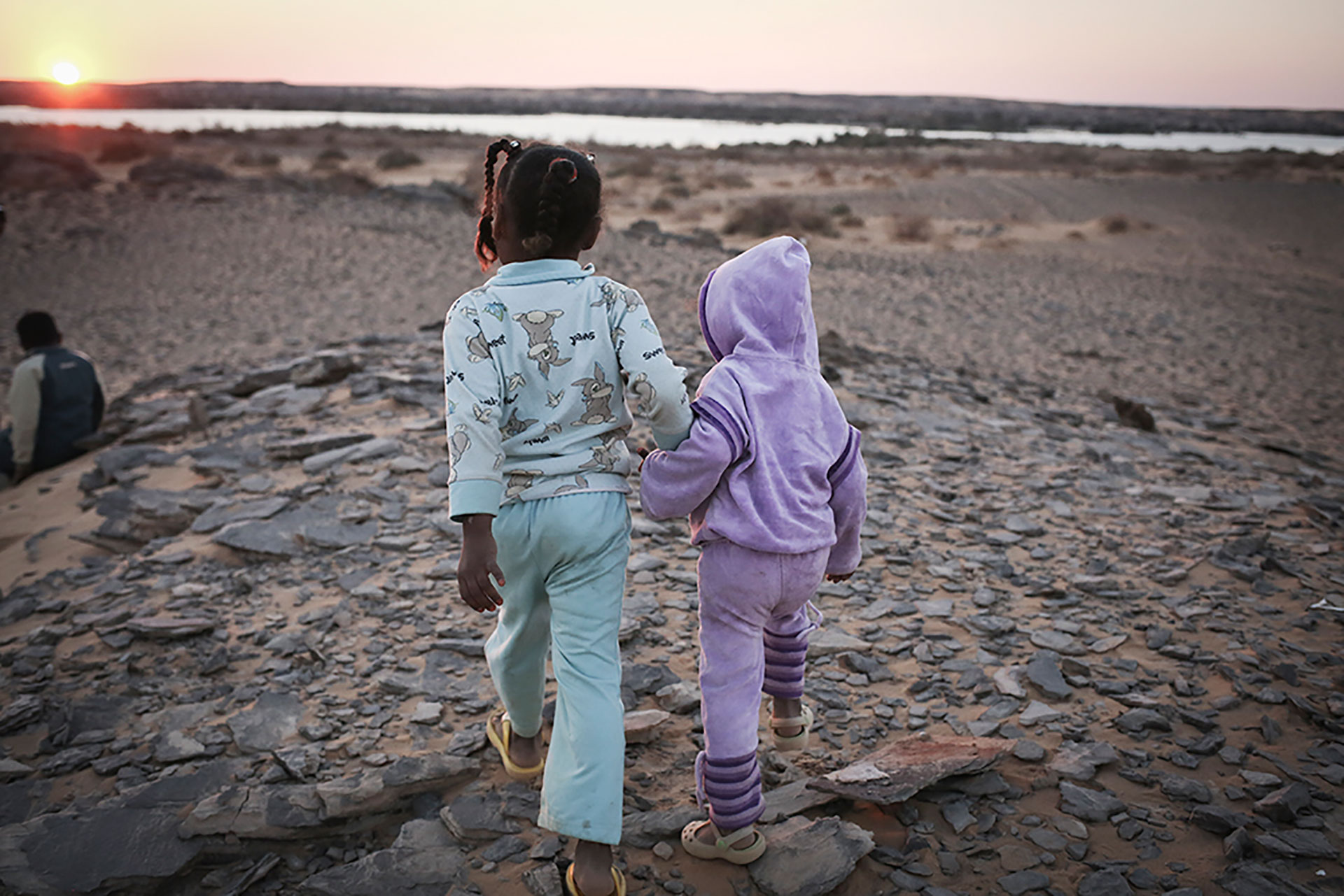 Children walk to the edge of the Nile at sunset, where Nubians used to have their homes, but no longer.