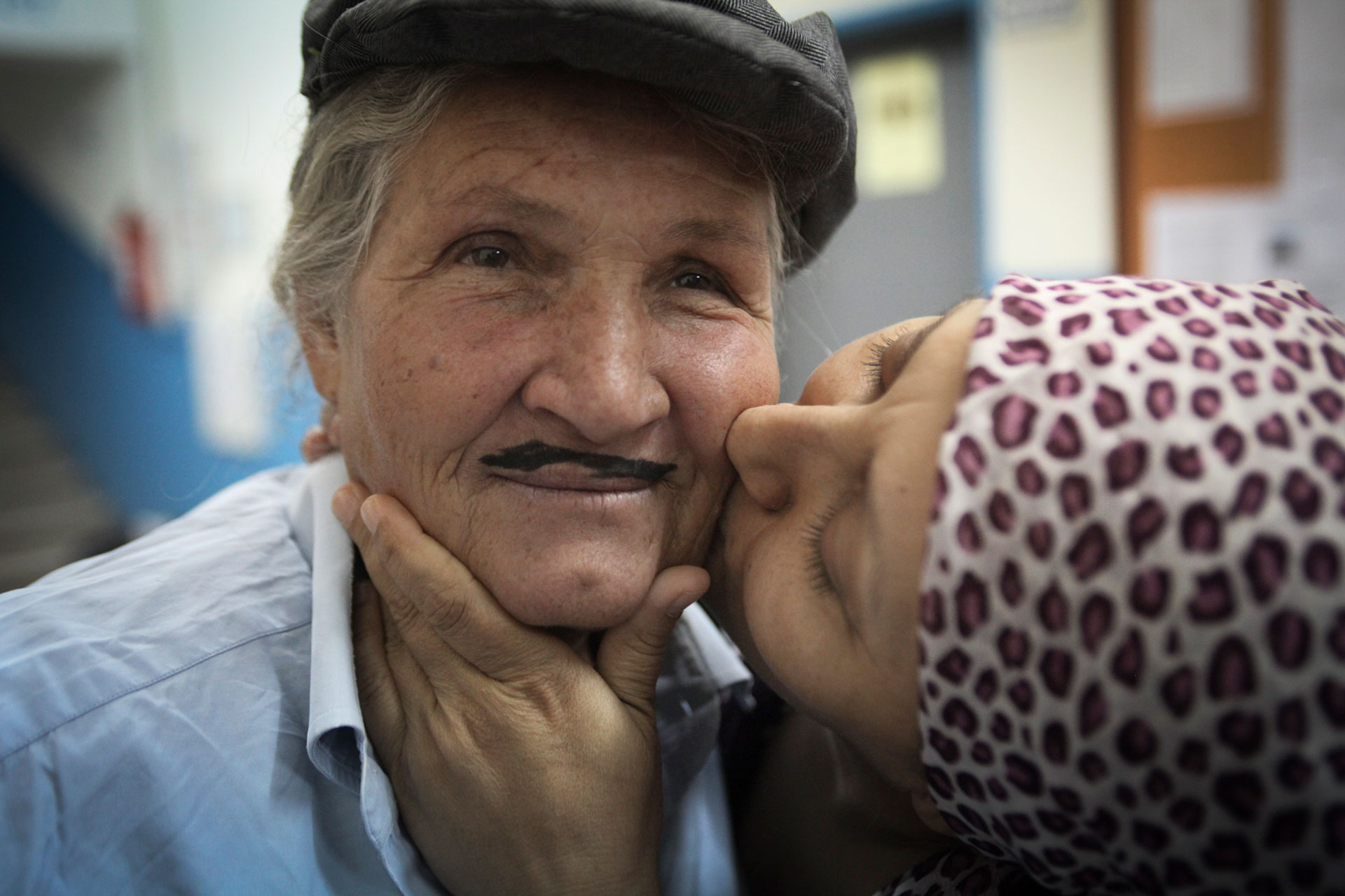 Cennet Sener, right, an actress in the Arslankoy Theater Group, playfully kisses another member of their troupe before their show, in a small village outside of Adana, southern Turkey.